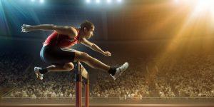 Male athlete hurdling on sports race